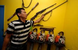 Environment activist Robert Chan points to confiscated firearms at the Palawan NGO Network in Puerto Princesa