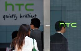 People walk past High Tech Computer Corp. HTC logos