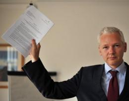 Wikileaks founder Julian Assange holds a legal document