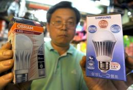 A South Korean worker holds up a Samsung light emitting diode (LED) bulb (R) and an Osram LED bulb (L)
