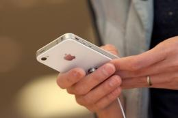 A customer looks at an iPhone 4 at the Apple store in Palo Alto, California