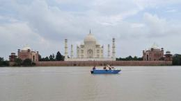 Agra police officials inspect the water level of the Yamuna river as it passes the Taj Mahal