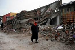 A homeless survivor walks by a collapsed building after an earthquake in Ercis, Turkey
