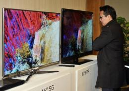 A journalist compares the 3-D televisions of Samsung(L) and LG(C) in Seol