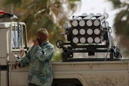 A Libyan rebel stands near a rocket launcher in the western gate of Ajdabiya