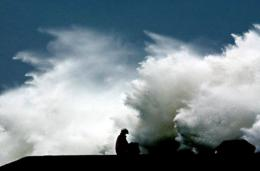 A local resident holds an umbrella while a giant wave hits the shore in Taiwan in 2002