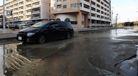 A lone car rests among the remain of water on a street in Chiba city