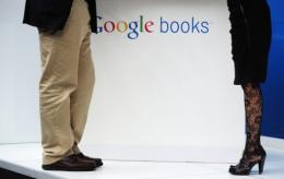 A man and a woman stand at a Google stand, next to a