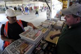A man buys a copy of the British tabloid newspaper News of the World