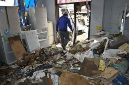 A man clears rubble from his destroyed shop in the city of Ofunato
