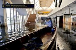 A man drives his boat inside Don Muang airport in Bangkok
