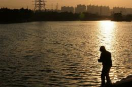 A man fishes from a canal in east Beijing in 2010