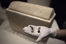 A man shows two Roman nails next to a Roman period ossuary
