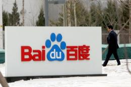 A man walks by a sign for China's top Internet search engine Baidu's office in Beijing