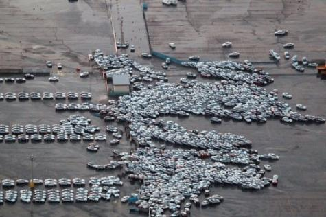An aerial shot shows vehicles ready for shipping being carried by a tsunami tidal wave at Hitachinaka city in Japan