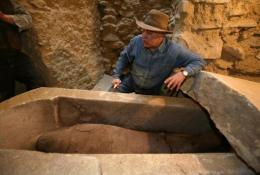 An archaeoligst inspects an Egyptian sarcophagus containing a mummy