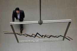 An employee walks by an index sculpture in the Hellenic Exchanges