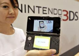 A Nintendo employee displays a portable videogame console with a 3D display called the