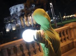 A performer wearing a green outfit displays an electric bulb-shaped lantern in Romania
