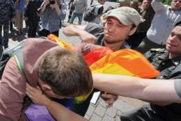 A Russian policeman (R) tries to stop a man (C) hitting a gay rights activist in central Moscow on May 28