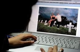 A student views an online photo album on the social networking site Facebook