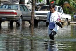 A Thai woman walks through floodwaters in Bangkok on Friday