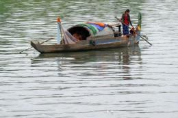 A woman rows a boat along the Mekong river in Phnom Penh