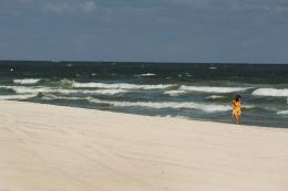 A woman walks along the deserted beach in Gulf Shores, Alabama, in 2010