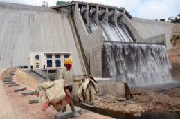 A worker carries empty cement bags across the front of the Kamchay dam at today's inauguration ceremony