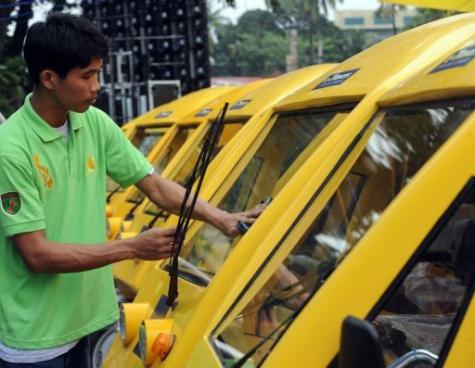 A worker cleans electric tricycles prior to the vehicles launch program in Manila