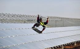 A worker installs panels at a photovoltaic power plant in Crucey-Villages, France