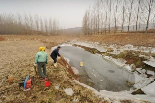 Chinese farmers prepare to pump water from a drying up reservoir at a well in eastern China