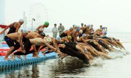 Competitors dive at the start of the men's 10km open water swimming event