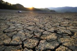 Cracked mud is pictured at sunrise in the dried shores of Lake Gruyere affected by continous drought in Europe