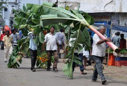 Indian men buy banana leaves at a market in Hyderabad this week on the eve of Diwali, the festival of lights