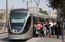 Israelis gather to board a train on the Jerusalem light rail system's first day of operation today