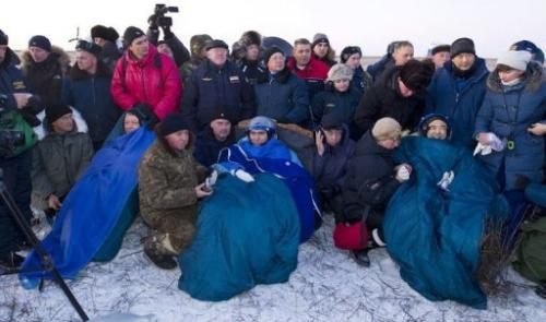(L-R) Mike Fossum, Sergei Volkov and Satoshi Furukawa sit swathed in blue rugs and blankets moments after they land