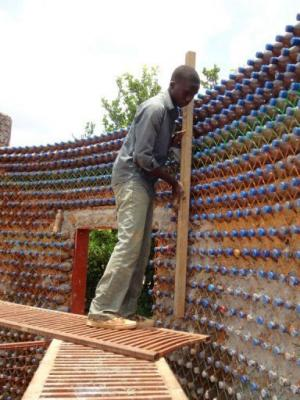 Nineteen-year old mason, Yahaya Musa, checks a wall of made of sand-filled plastic bottles