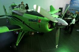 Participants look at a 100% ethanol powered aircraft made by Brazilian jet manufacturer Embraer