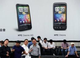 People stand under an advertisement showing HTC smartphones in Taipei in April