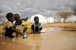 Somali boys fetch water from a puddle that formed after rain at the Dadaab refugee complex in Kenya