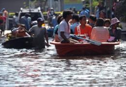 Thai people commute through floodwaters in Bangkok on Friday
