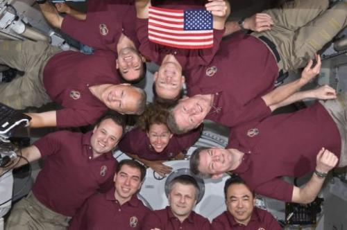The Expedition 28 crew and the STS-135 Atlantis astronauts in a microgravity circle