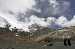 Tibetan women stand at the foot of a glacier in 2007