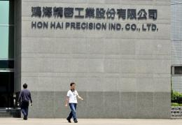 Workers walk in front of Taiwanese electronics giant Hon Hai's headquarters in Tuchung city