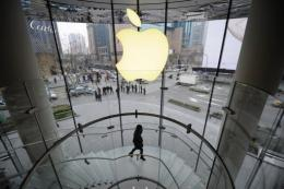 A customer walks under an Apple logo sign in in Shanghai in February 22