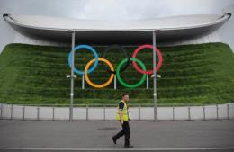 A man walks past Olympic rings outside the Aquatic Centre at the London 2012 Olympic Park in east London