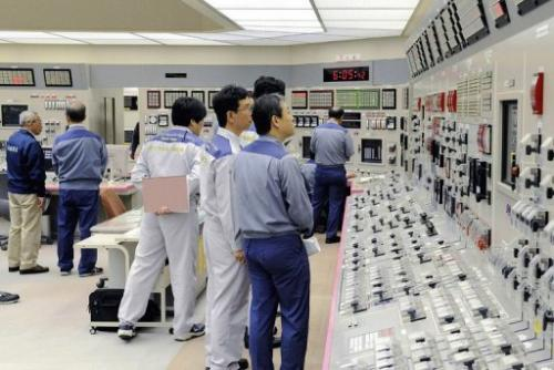 Kansai Electric Power Co (KEPCO) engineers check readings at the company's Oi nuclear power plant
