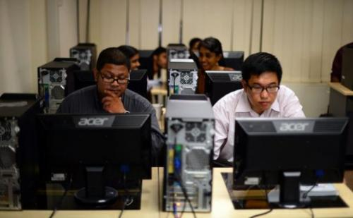 Students prepare for an exam in front of their computers at Kuala Lumpur-based Asia e University