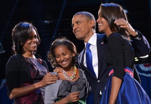 US President Barack Obama accompanied by First Lady Michelle and their daughters appears on stage on election night